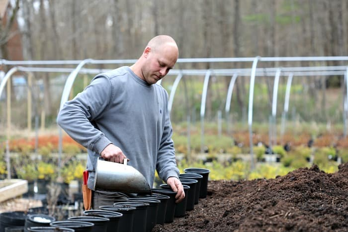 man holding silver scooper and filling black pots with potting mix