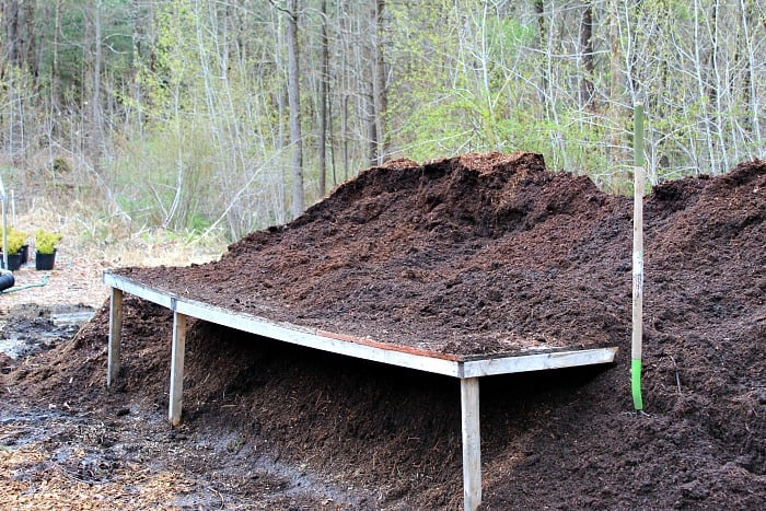 wooden table on top of big pile of potting mix